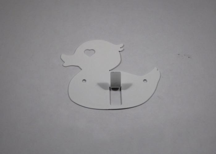 Hängare / Krok i plåt, figurskuren i formen av en badanka. Vit.