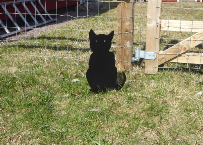 Siluett i form av en sittande svart katt som är nedstucken i marken.