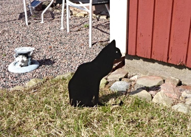 Siluett i form av en svart katt som sitter på sin svans och är nedstucken i marken.