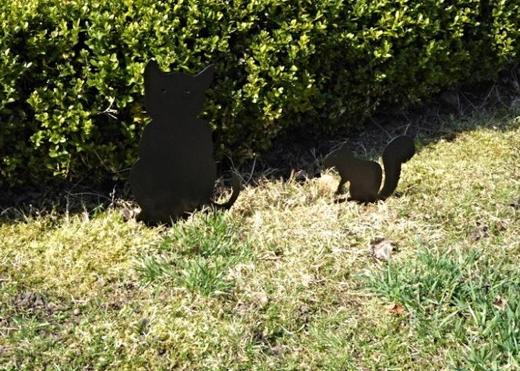 Sittande svart katt och en svart ekorre i plåt som är nedstuckna i marken.