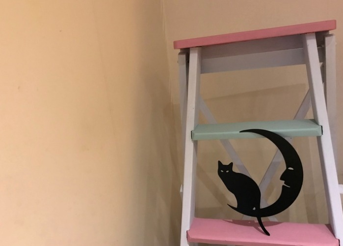 Sittande katt på en måne i plåt, svartlackerad.