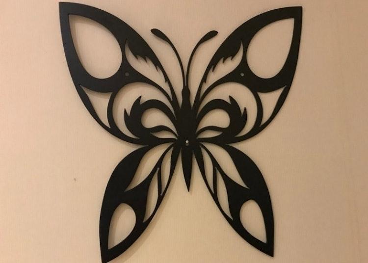 Fasaddekoration, en svart fjäril i plåt.