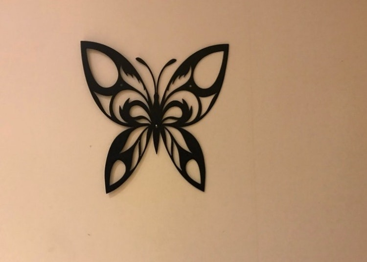 En fjäril i plåt, svart.