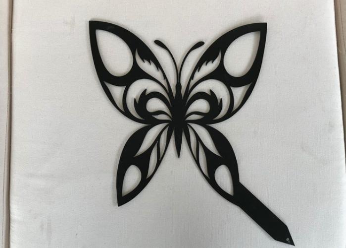 En fjäril i plåt med en spets.