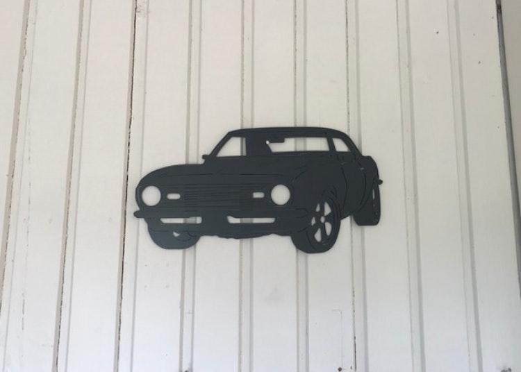 Väggdekoration i form av en Chevrolet Camaro-68 som är svart och i plåt.
