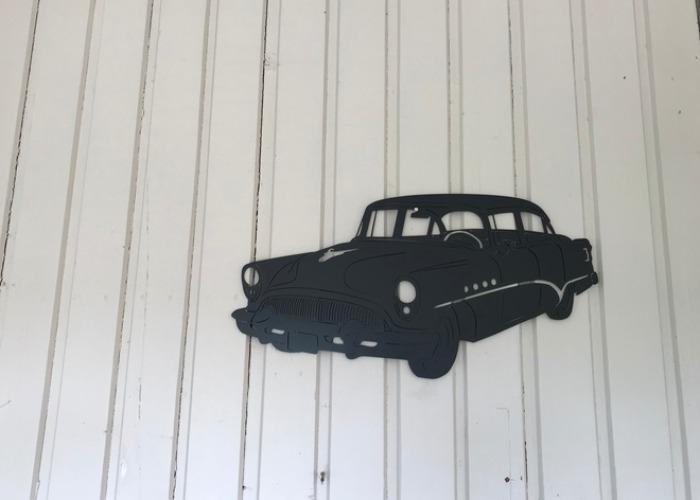 Väggdekoration i form av en Buick Roadmaster -54 som är svartlackerad i stålplåt.
