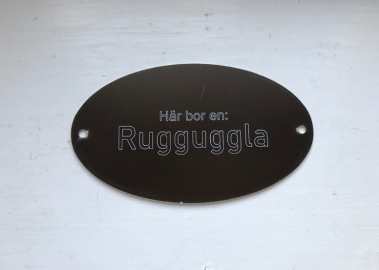 Graverad skylt i aluminium med texten Här bor en Rugguggla.