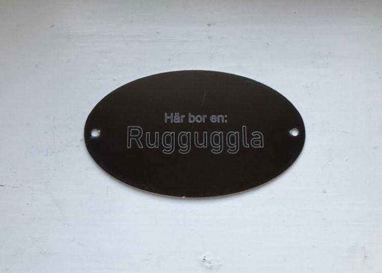 Skylt i aluminium med texten Här bor en Rugguggla.