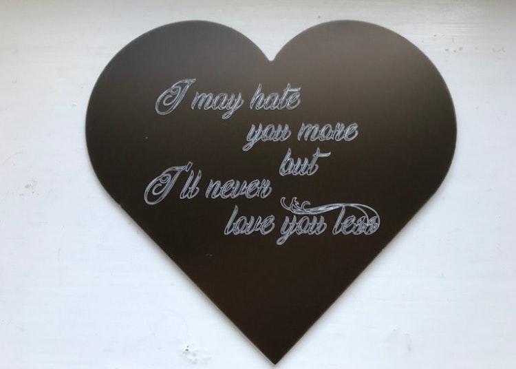 Hjärtformad skylt i aluminium med kärlekstext på engelska.