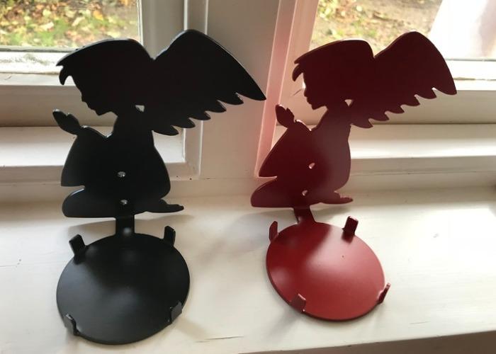 Två stycken väggljushållare i form av änglar i plåt.