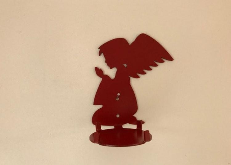 En röd ljushållare i plåt i form av en ängel.