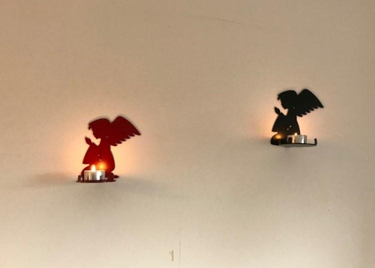 En röd och en svart ängel i plåt. Ljushållare som fungerar både till värmeljus och blockljus.