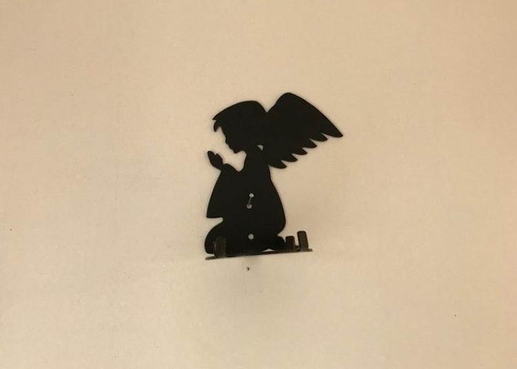 En svart ängel som sätts på väggen som ljushållare.