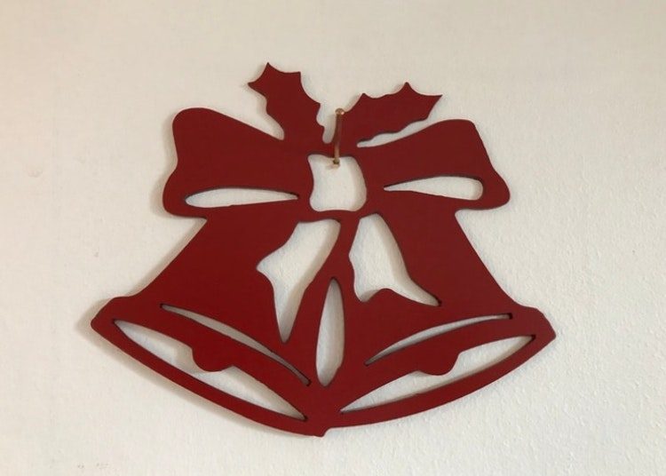 Röda julklockor i plåt att sätta upp på väggen.