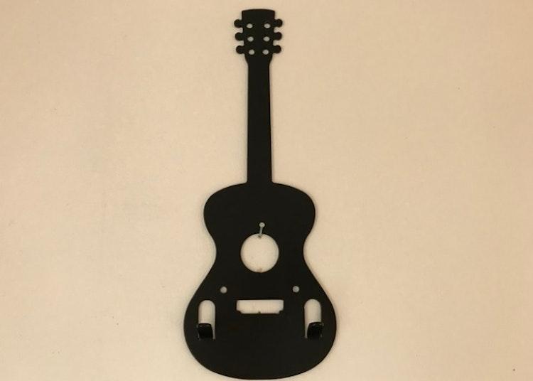 Svart gitarr i plåt med 2 stycken krokar.