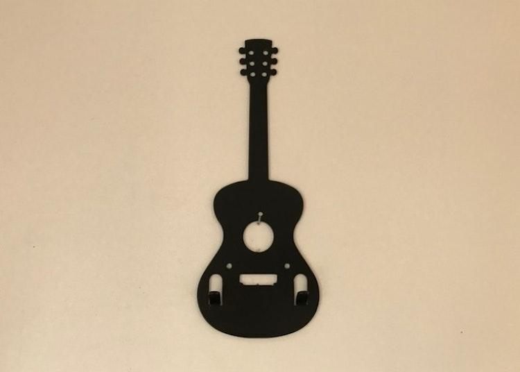 Svart hängare i form av en gitarr med två stycken krokar.