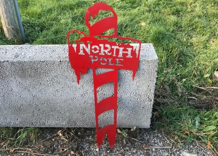 North pole stolpe i plåt som trädgårdsdekoration.