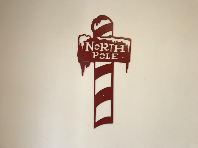 Röd stolpe i plåt med texten north pole att hänga på väggen.