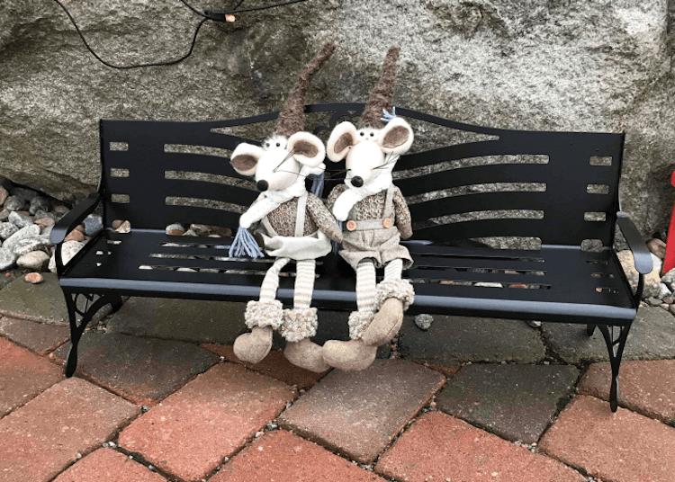 Två gosedjur sittandes på en liten parkbänk i plåt.