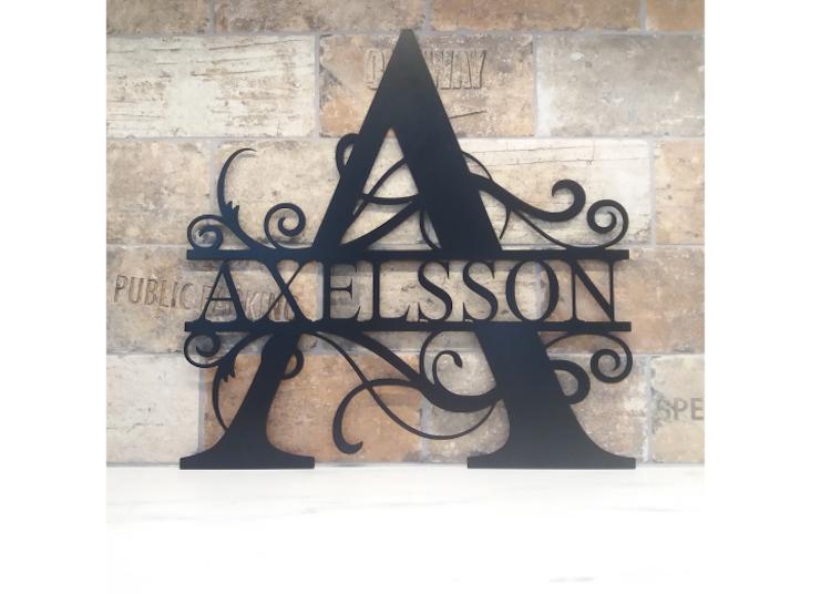 Svart split monogram med namnet Axelsson mot tegelvägg.