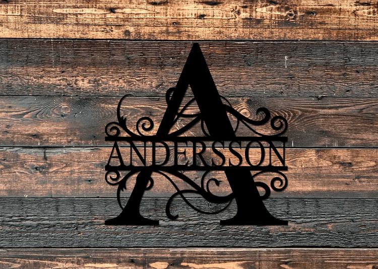 Svart splitmonogram med namnet Andersson, på trävägg.