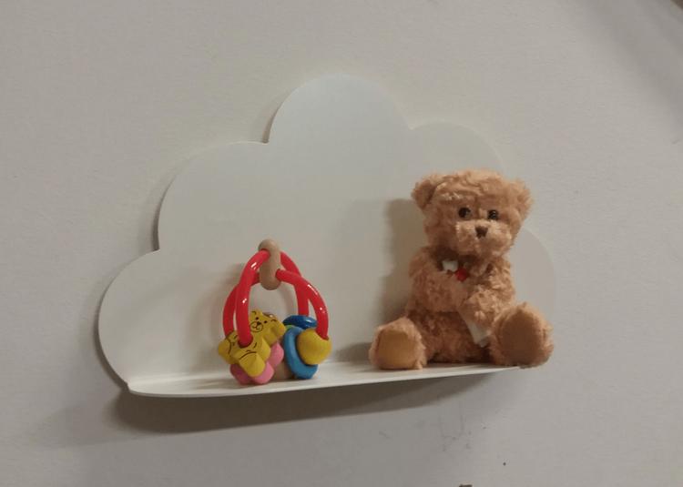 Vit molnhylla i plåt, med en nalle och en barnleksak.