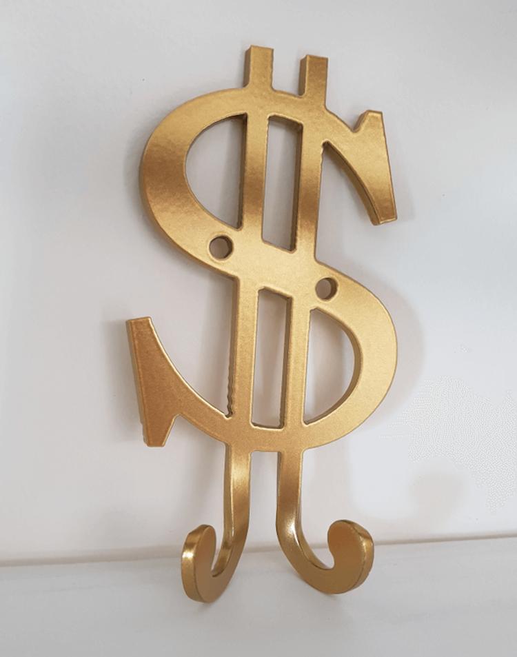 Vägghängare i form av ett guldfärgat dollartecken.