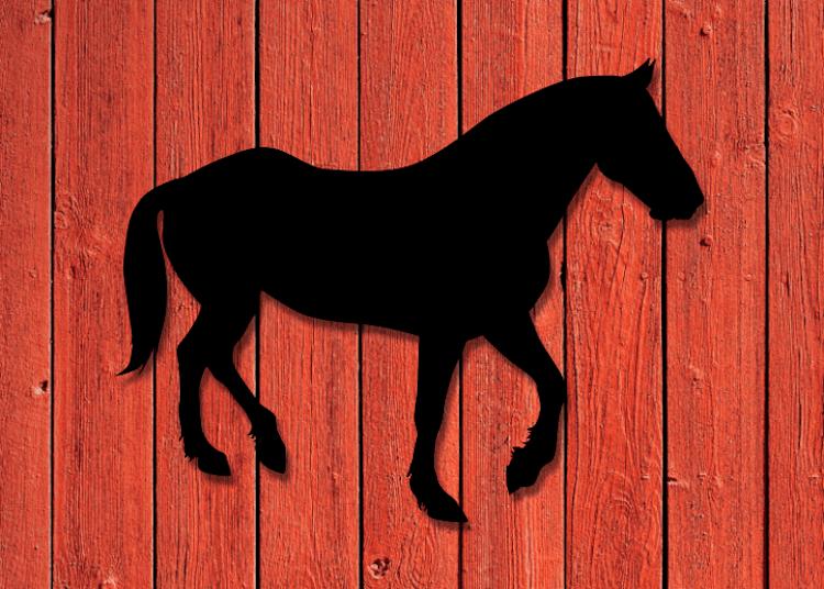 Svart siluett av häst på röd träfasad.