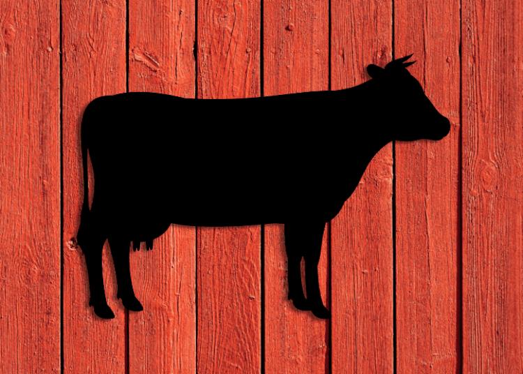 Svart siluett av ko på röd träfasad.