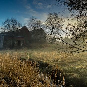 Forlatt gård i solnedgang