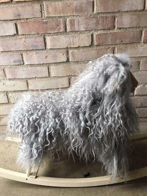 GUNGFÅR i grå långhårigt,krulligt fårskinn