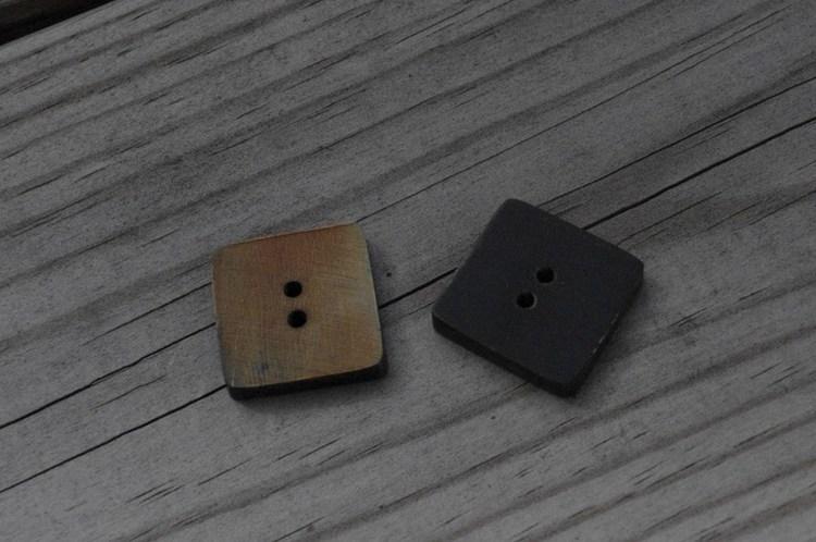 Fyrkantig knapp i horn. Ca 2x2 cm.
