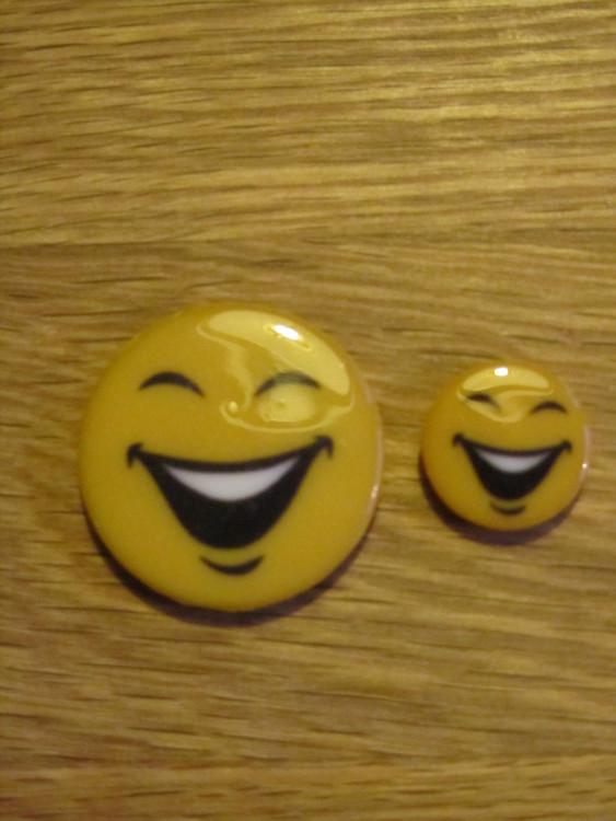Fräck knapp med skrattande Smiley. Knappen finns i två storlekar, 15 och 28 mm, och är undersydd.