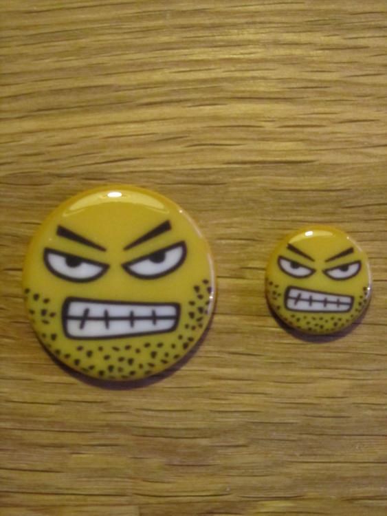 Fräck knapp med arg Smiley. Knappen är undersydd och finns i två storlekar, 15 och 28 mm.