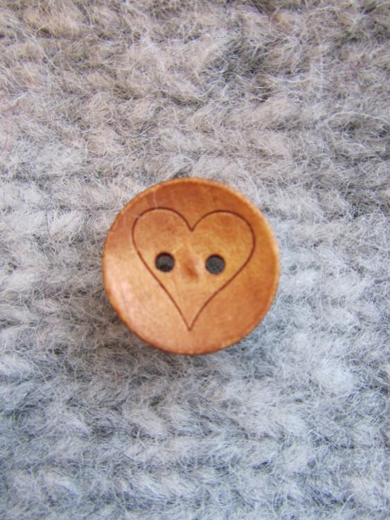Den här fina träknappen med ett hjärta passar jättebra till alla stickade och virkade barnplagg. Knappen är 18 mm i diameter och har två hål.