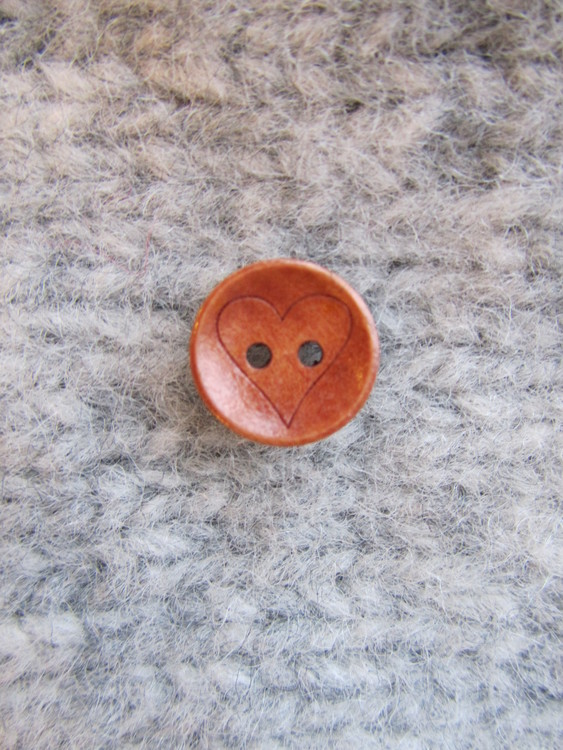 Den här söta träknappen med ett hjärta passar jättebra till alla stickade och virkade barnplagg. Knappen är 15 mm i diameter och har två hål.
