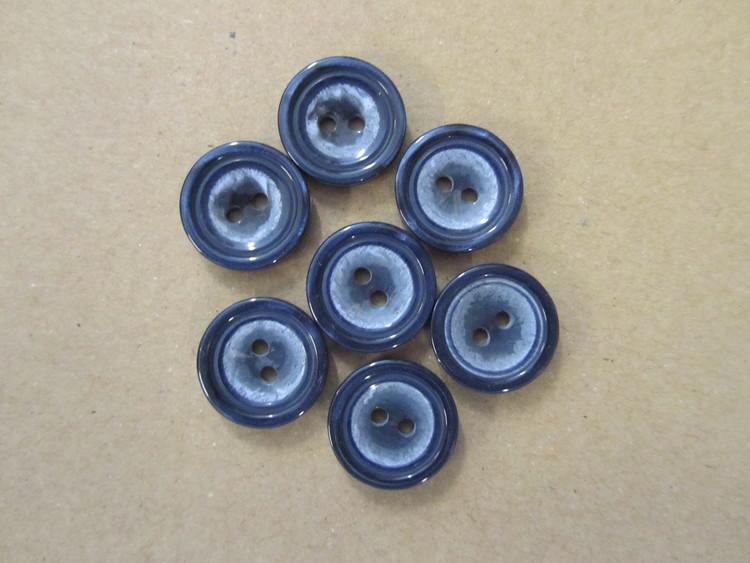 Rund, blå knapp med två hål. Storlek 18 mm