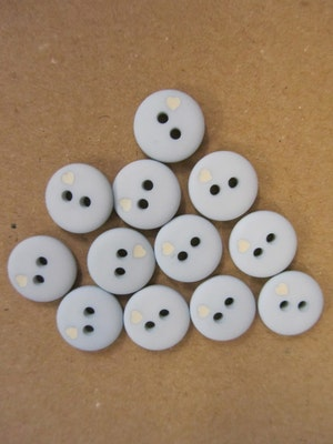 Ljusblå knapp med litet vitt hjärta - 12 mm