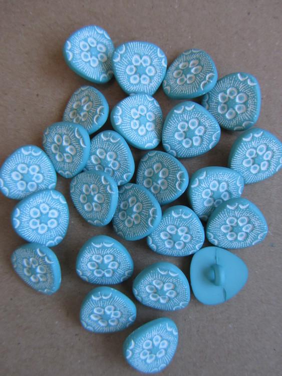 Turkos, trekantig knapp med mönster. Undersydd. Storlek 15 mm.
