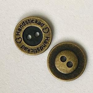 Metallnapp med text Handstickad. Antik mässing. 15 mm