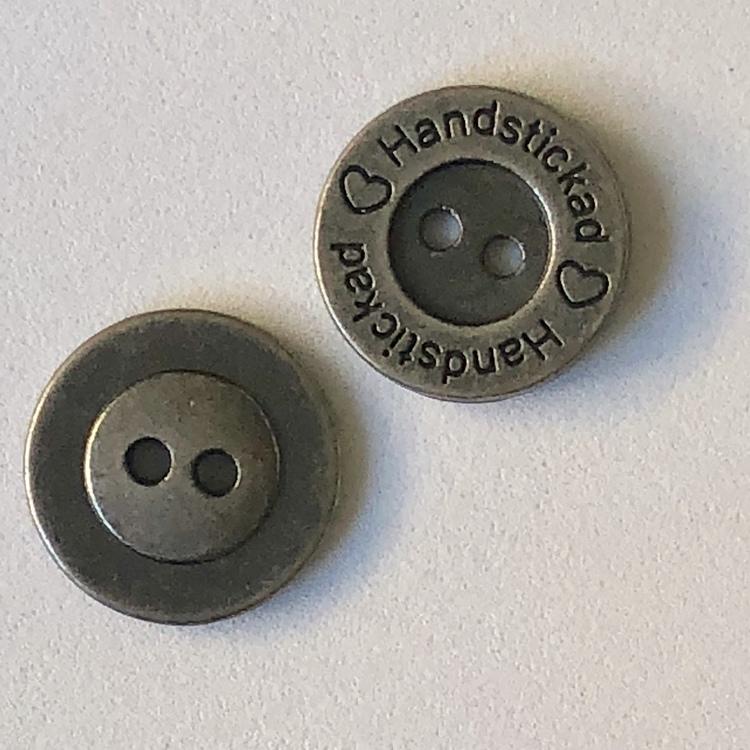 Metallnapp med text Handstickad. Färg: Antik silver. Storlek 15 mm.