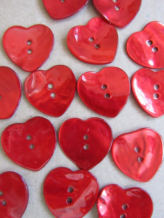 Röd pärlemorknapp Hjärta. Två hål. Storlek 40 mm.