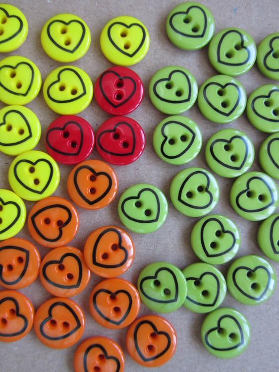Rund knapp, grön, röd, gul och orange, med hjärtan i svart. Två hål. Storlek 13 mm.