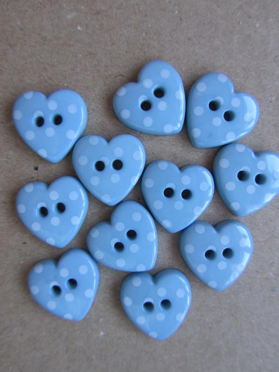 Ljusblå knapp Hjärta med vita prickar. Två hål. Storlek 24 mm.