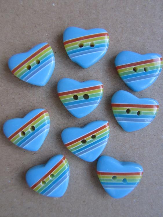 Blå knapp Hjärta med regnbågsfärger. Två hål. Storlek 20 mm.