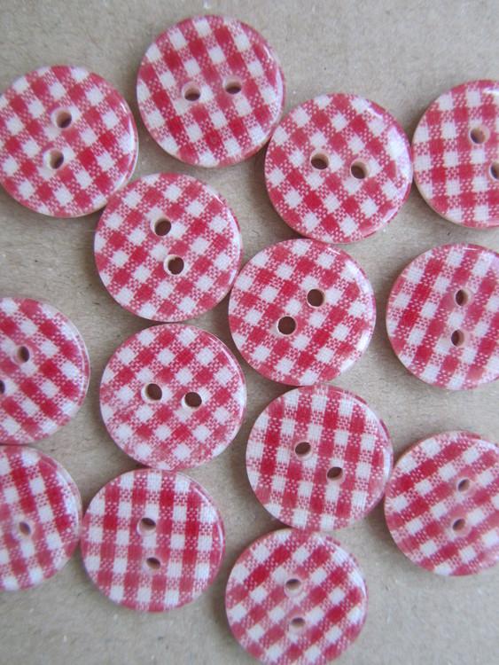 Röd- och vitrutig knapp. Två hål. 18 mm.