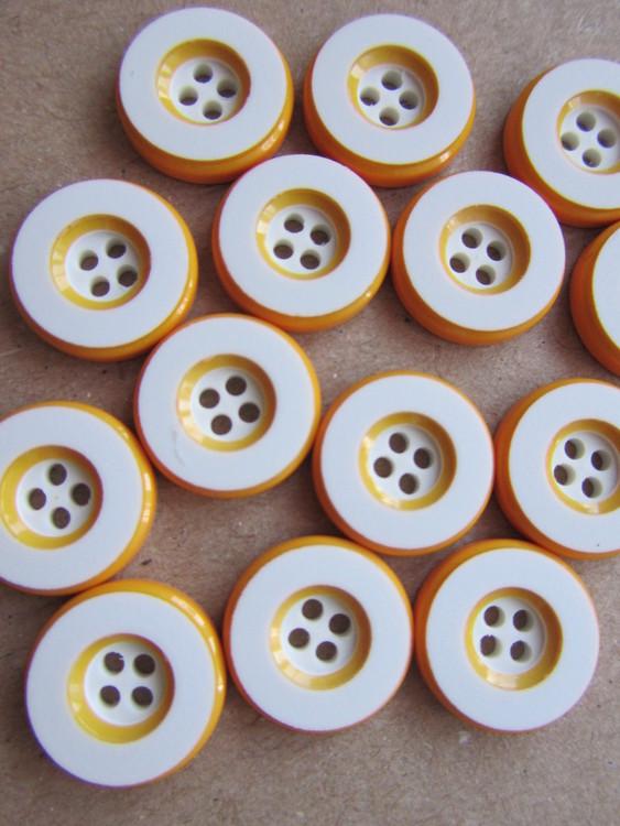 Vit knapp med gul kant. Fyra hål.Storlek 14 mm.