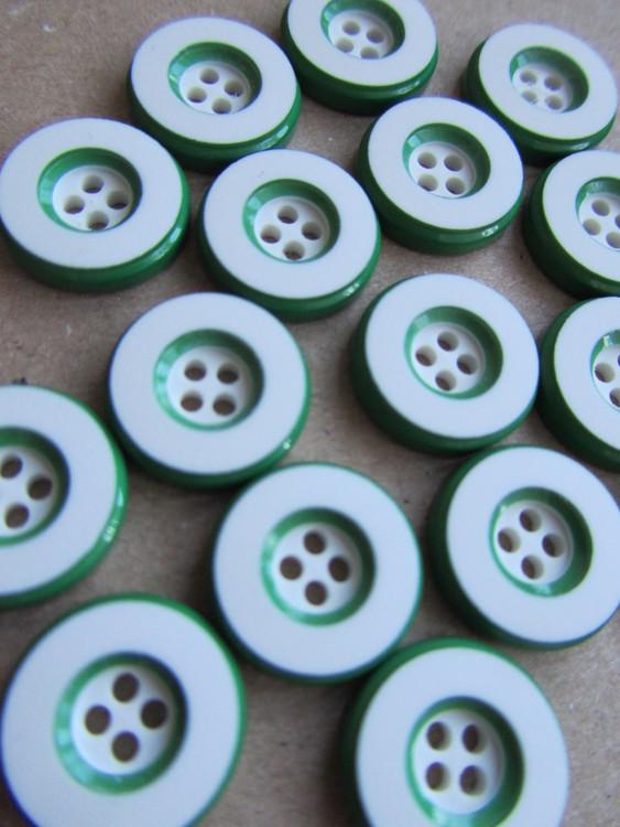 Vit knapp med grön kant. Fyra hål.Storlek 14 mm.