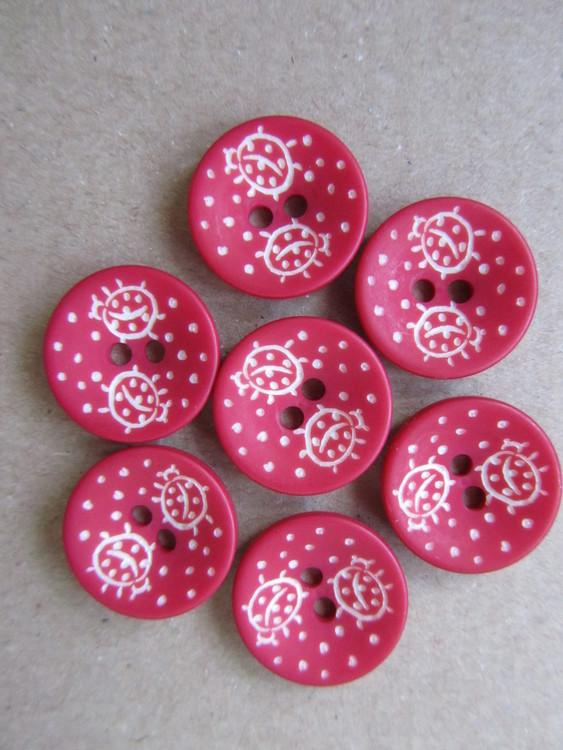 Röd knapp med Nyckelpigor. Två hål. Storlek 15 mm.