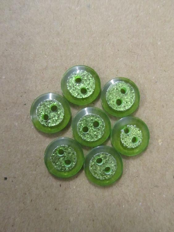 Grön knapp med glitter. Två hål. Storlek 12 mm.